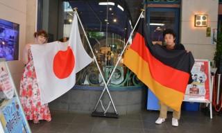 Deutschland Platz 2: Claudia Kühlewindt -   Auf dem Bild sieht man super, wie Deutschland und Japan aufeinander treffen. Ich - Deutsche - mit der japanischen Flagge, sowie mein Freund - Japaner - mit der deutschen Flagge (und auch Deutschland-Tshirt, aber das sieht man nicht). Aufgenommen wurde das Bild in Yokohama vor dem Shinyokohama Ramen Museum. Auch dort trifft Deutschland auf Japan, denn innen gibt es das Mukku Zweite, ein deutsches Ramen-Restaurant mit Ursprung in Frankfurt. Dort gibt es u.a. Ramen mit Kassler und Sauerkraut.